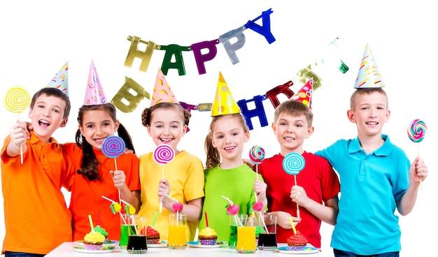 Groep gelukkige kinderen met kleurrijke snoepjes met plezier op het verjaardagsfeestje - geïsoleerd op een witte