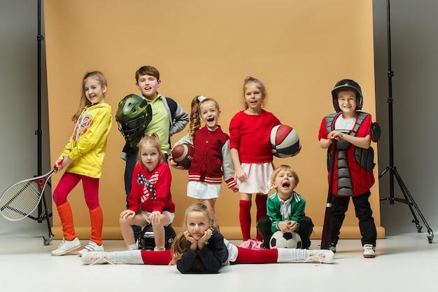 Groep gelukkige kinderen toont verschillende sporten. studio mode-concept. emoties concept. jongens en meisjes houden van sporten. voetbal, amerikaans voetbal, honkbal, tennis en gymnastiek. modeshow voor kinderen.