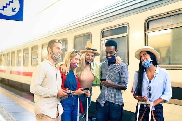 Groep gelukkige lachende jonge mensen met behulp van mobiele telefoons in het treinstation