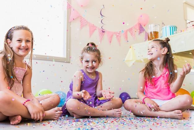 Groep gelukkige meisjes die met confettien tijdens verjaardagspartij spelen
