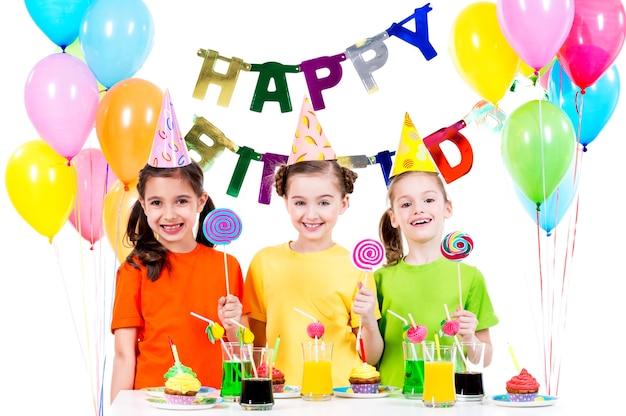 Groep gelukkige meisjes met kleurrijke snoepjes met plezier op het verjaardagsfeestje - geïsoleerd op een witte