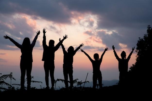 Groep gelukkige mensen die bij de zomerzonsondergang spelen in aard