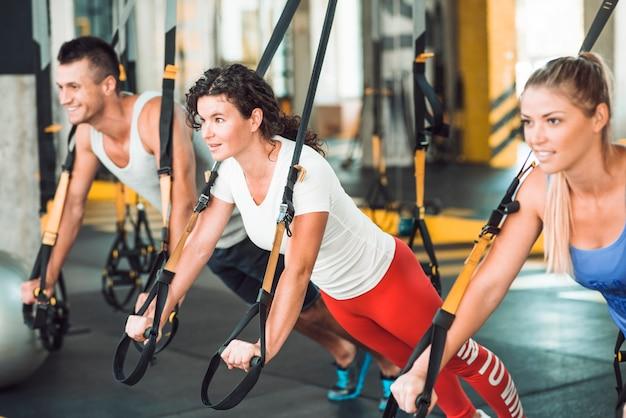 Groep gelukkige mensen die oefening met geschiktheidsriem doen in gymnastiek