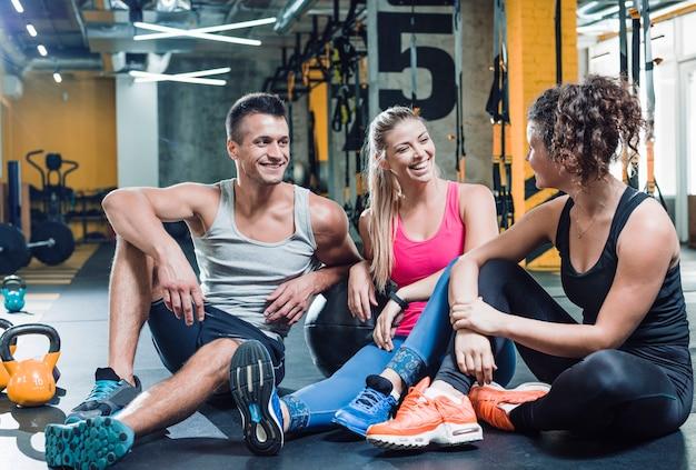 Groep gelukkige mensen die op vloer na training zitten