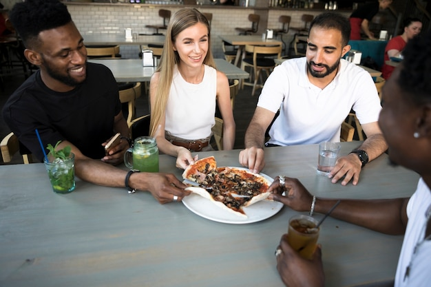 Groep gelukkige mensen die pizza eten