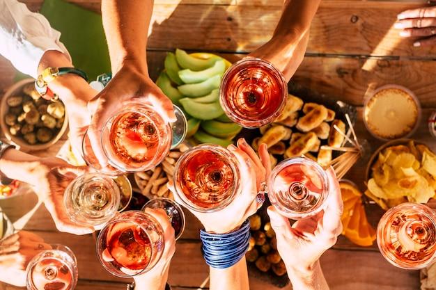 Groep gelukkige mensen die samen met kopjes rode wijn roosteren onder het zonlicht op een zonnige dag