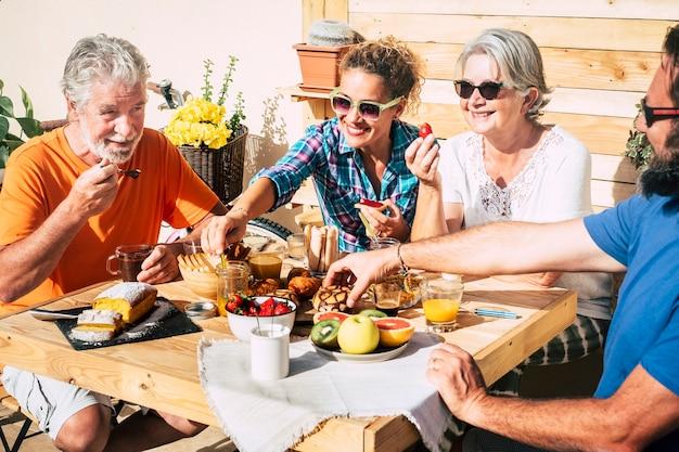 Groep gelukkige mensen die thuis op het terras ontbijten samen met liefde - dochter, zoon, oma en opa eten en drinken - paar senioren getrouwd en volwassenen