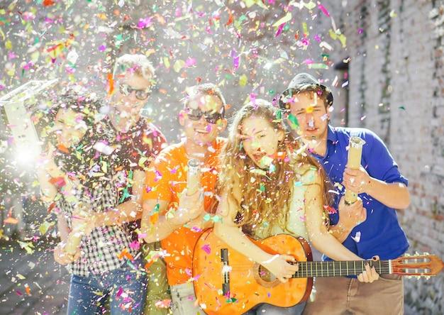 Groep gelukkige mensen gooien confetti, gitaar spelen, zingen en dansen op straat