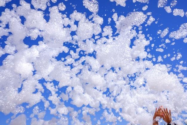 Groep gelukkige mensen heffen hun handen op tijdens een schuimfeest in de zomer om met zeepbellen te spelen.