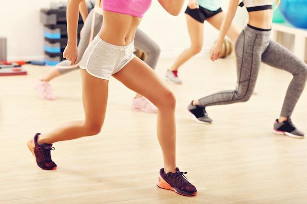 Groep gelukkige mensen met coach dansen in sportschool