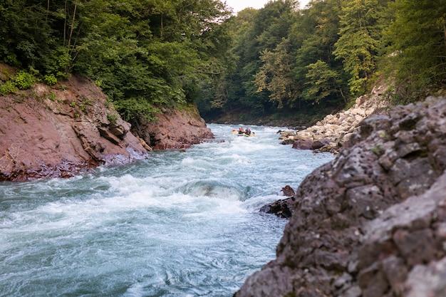 Groep gelukkige mensen met gids whitewater die en op rivier raften roeien.