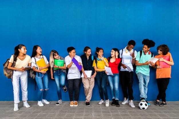 Groep gelukkige multiraciale tiener middelbare scholieren praten en lachen voordat de klas rugzakken draagt en folders vasthoudt. terug naar schoolconcept