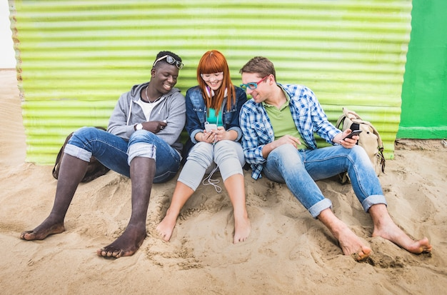 Groep gelukkige multiraciale vrienden die pret hebben die samen mobiele slimme telefoon met behulp van