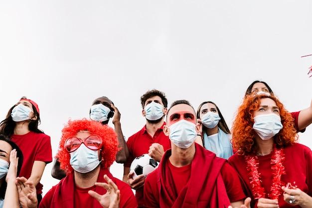 Groep gelukkige multiraciale vrienden in beschermend gezichtsmasker ter ondersteuning van hun team