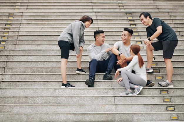 Groep gelukkige opgewonden vietnamese jonge mensen die op trappen zitten en training bespreken en grappen maken