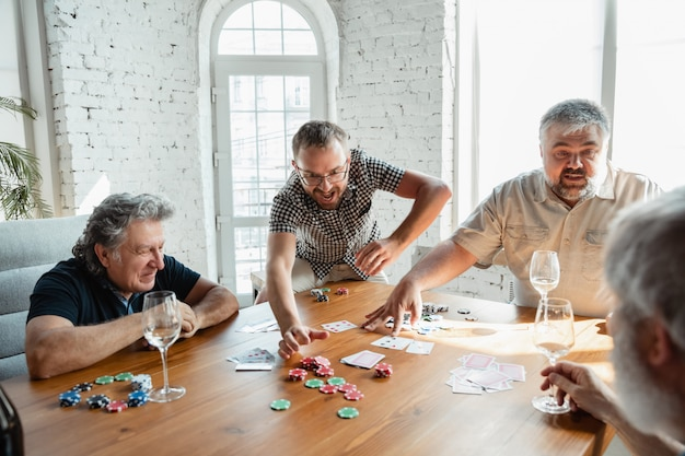 Groep gelukkige rijpe vriendenspeelkaarten en het drinken van wijn