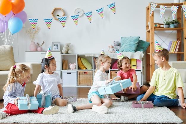 Groep gelukkige schattige kinderen in verjaardag caps zittend op een tapijt terwijl ze hun geschenken thuisfeest gaan uitpakken