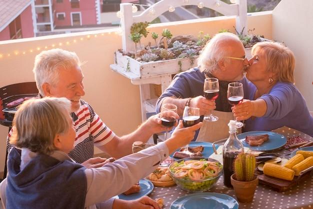 Groep gelukkige senior oude mensen hebben samen plezier tijdens de lunch of het diner thuis op het buitenterras