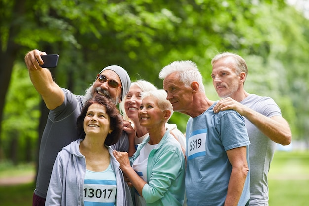Groep gelukkige senior vrienden die deelnemen aan de zomer marathon race staan samen in bospark nemen selfie groepsfoto