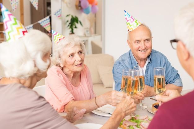 Groep gelukkige senior vrienden rammelende met fluiten champagne door geserveerd tafel