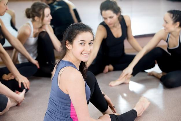 Groep gelukkige sportieve jonge vrouwen die chatten op pauze in sportzaal
