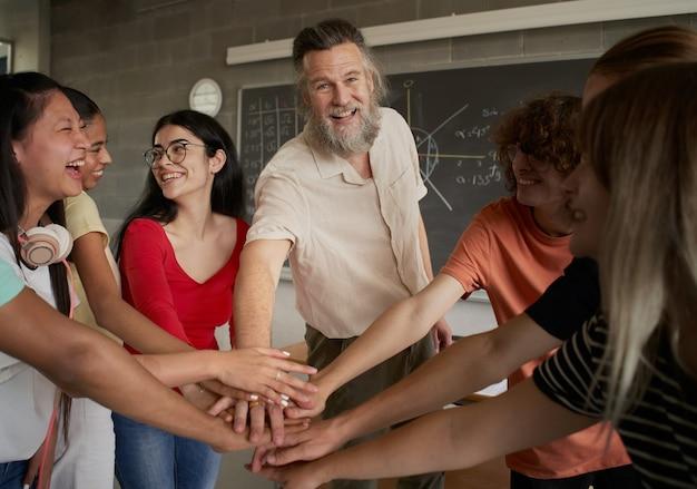 Groep gelukkige studenten die de hand steken met de leraar, de professor kijkt naar de camera