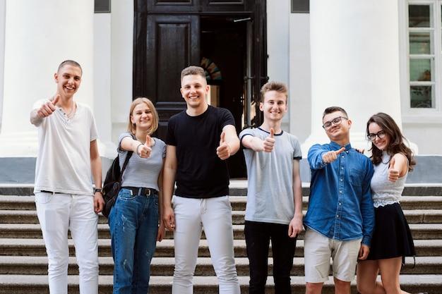 Groep gelukkige studenten die zich bij treden van conventionele universiteit bevinden, duimen tonen en aan de camera glimlachen