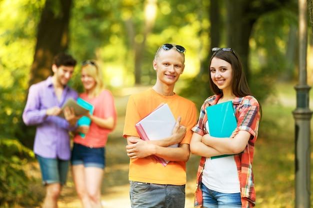 Groep gelukkige studenten met boeken in het park op een zonnige dag
