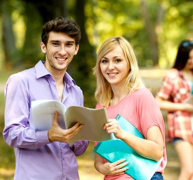 Groep gelukkige studenten met boeken in het park