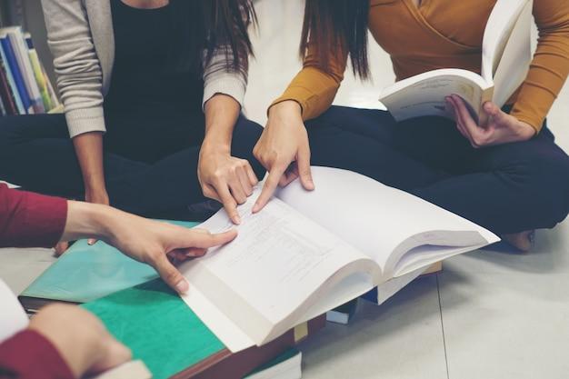 Groep gelukkige studenten met boeken praten en voorbereiden op examen in de bibliotheek. onderwijsconcept.