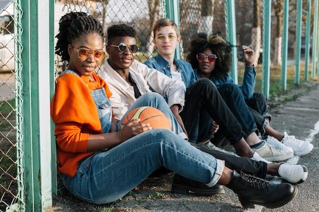 Groep gelukkige tieners die in openlucht stellen