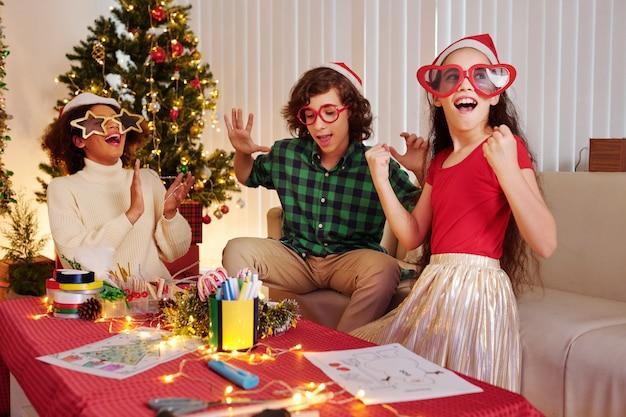 Groep gelukkige tieners in grappige glazen en kerstmutsen met een klein kerstfeestje thuis wanneer ze tekenen en versieringen maken