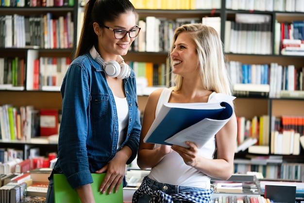 Groep gelukkige universiteitsstudenten die studeren in de universiteitsbibliotheek