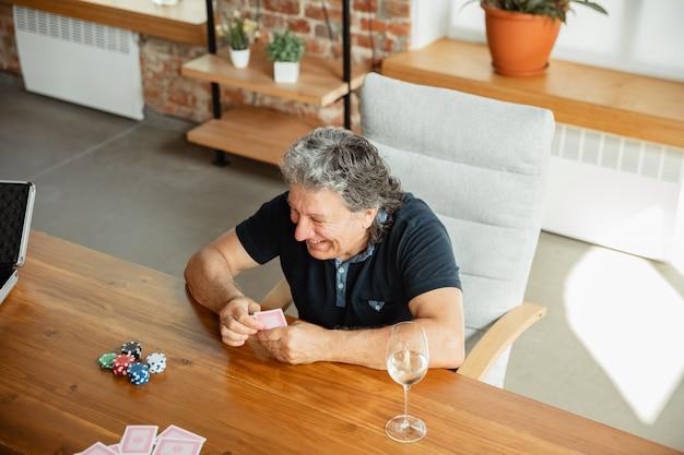 Groep gelukkige volwassen mensenspeelkaarten en het drinken van wijn