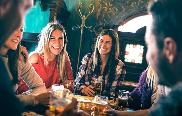 Groep gelukkige vrienden die bier drinken bij het restaurant van de brouwerijbar