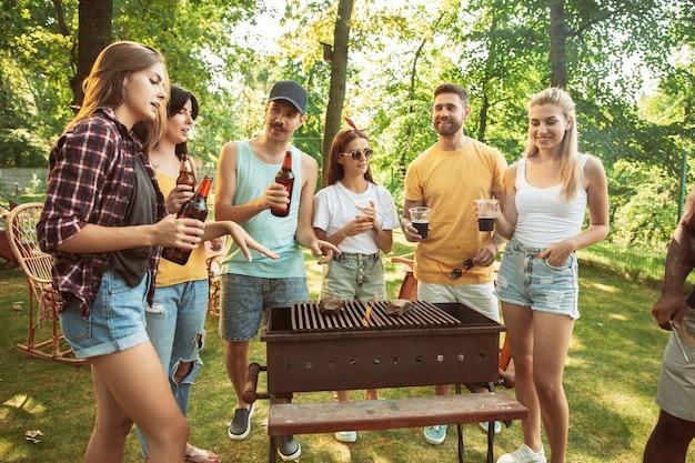 Groep gelukkige vrienden die bier en barbecuepartij hebben op zonnige dag. samen buiten rusten in een bos open plek of achtertuin. vieren en ontspannen, lachen. zomer levensstijl, vriendschap concept.