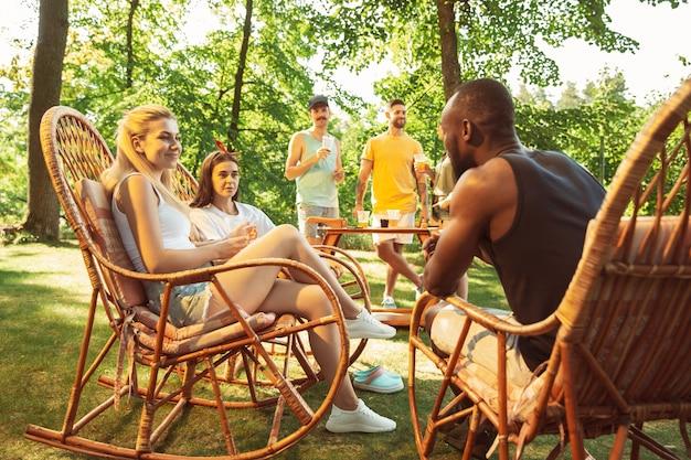 Groep gelukkige vrienden die bier en barbecuepartij hebben op zonnige dag. samen buiten rusten in een bos open plek of achtertuin
