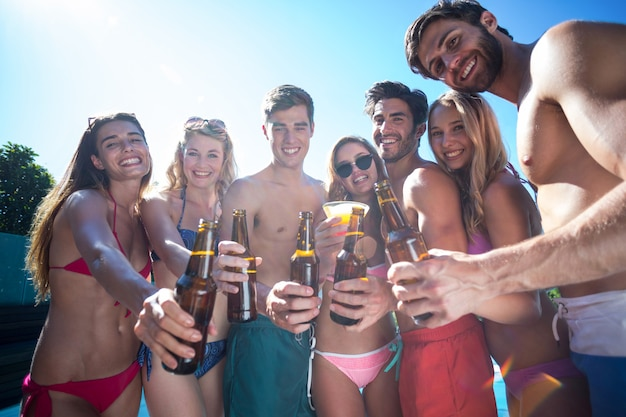 Groep gelukkige vrienden die bierflesjes tonen dichtbij het zwembad
