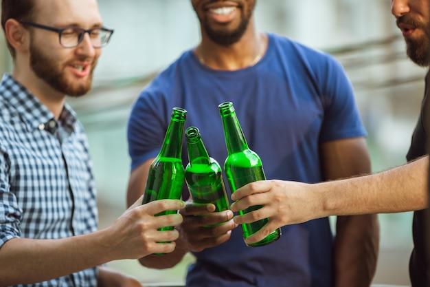 Groep gelukkige vrienden die bierpartij in de zomerdag hebben. samen buiten rusten, feesten en ontspannen, lachen. zomer levensstijl, vriendschap concept.