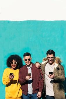 Groep gelukkige vrienden die de mobiel op straat gebruiken. vriendschapsconcept.