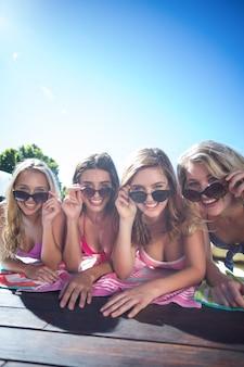 Groep gelukkige vrienden die dichtbij pool liggen