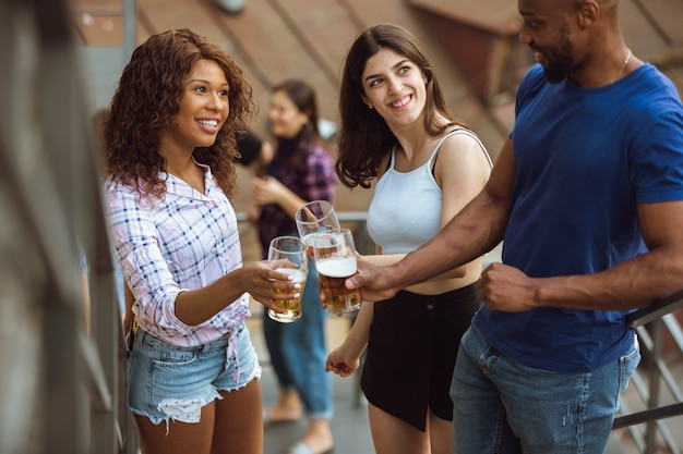 Groep gelukkige vrienden die een bierfeestje hebben in de zomerdag. samen buiten rusten, vieren en ontspannen, lachen. zomer levensstijl, vriendschap concept. rammelende bierglazen, vrolijk, blij.