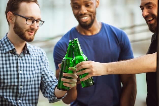 Groep gelukkige vrienden die een bierfeestje hebben in de zomerdag, samen rusten in de buitenlucht en vieren