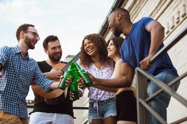 Groep gelukkige vrienden die een bierfeestje hebben in de zomerdag samen uitrusten buiten vieren