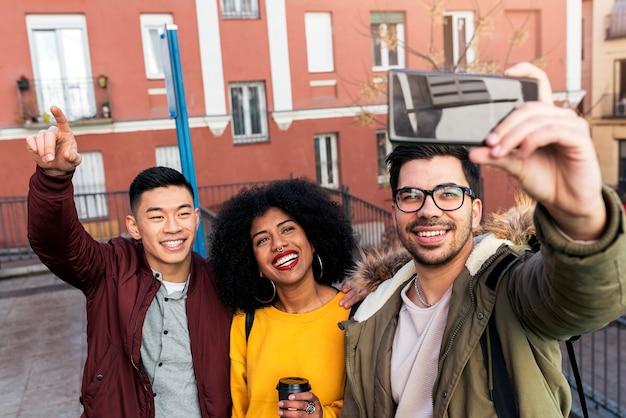 Groep gelukkige vrienden die een selfie op straat nemen. vriendschapsconcept.