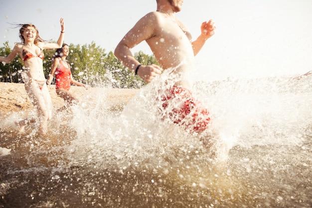 Groep gelukkige vrienden die in het water rennen - actieve mensen die plezier hebben op het strand op vakantie - toeristen die gaan zwemmen