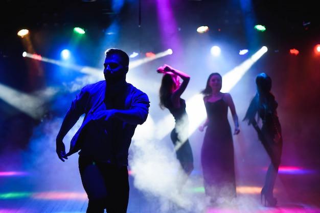 Groep gelukkige vrienden die in nachtclub dansen