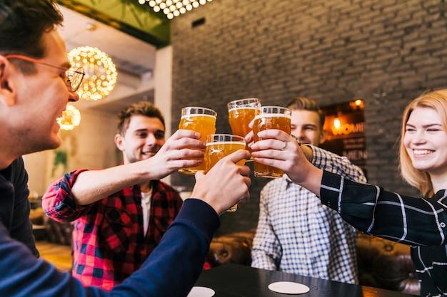 Groep gelukkige vrienden die met bierglazen toejuichen