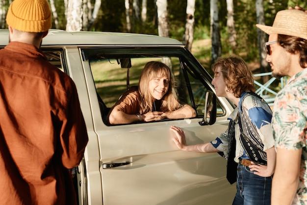 Groep gelukkige vrienden die met elkaar praten terwijl ze buiten staan en hun reis bespreken