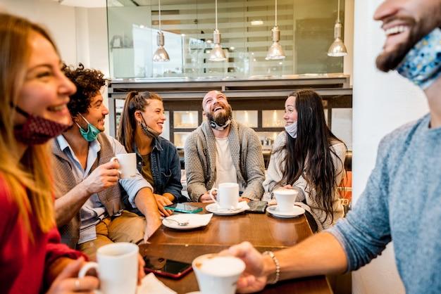 Groep gelukkige vrienden die met gezichtsmasker espresso drinken bij koffiehuis